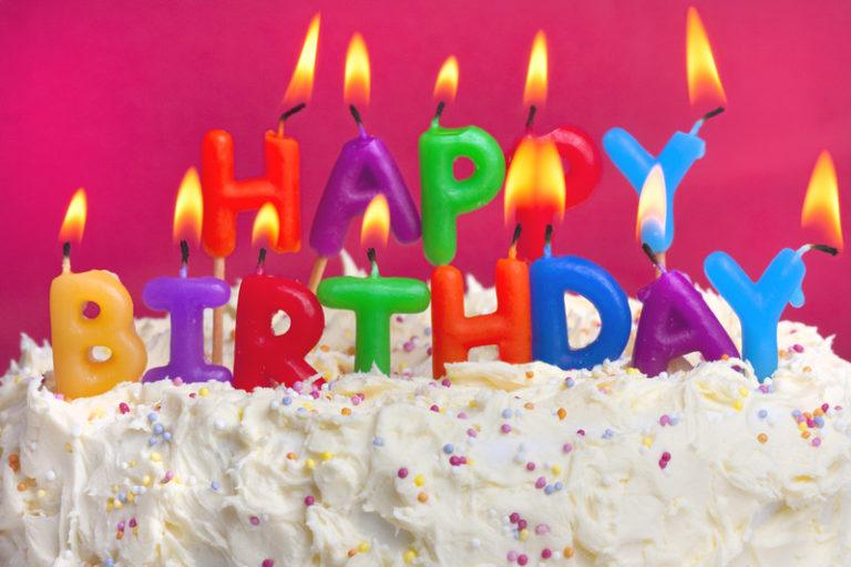 This photo shows a white cake with sprinkles and lit candles in various colors that spell out Happy Birthday in front of a magenta background, representing the best birthday affiliate programs.
