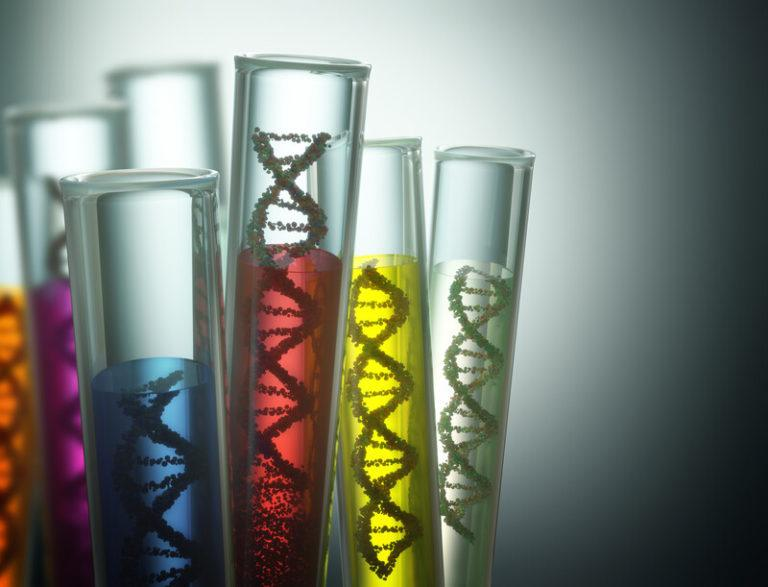 This photo shows a set of five test tubes against a white light and dark background, with each test tube containing strands of DNA in liquid colored maroon, blue, and yellow, representing the best genetic testing affiliate programs.