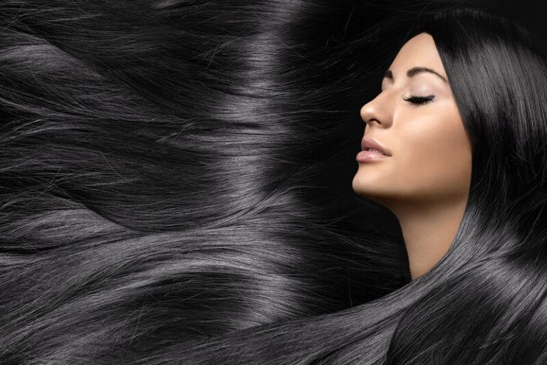 This photo shows a woman with closed eyes, whose dark hair flows through the entire photo, representing the best hair care affiliate programs.