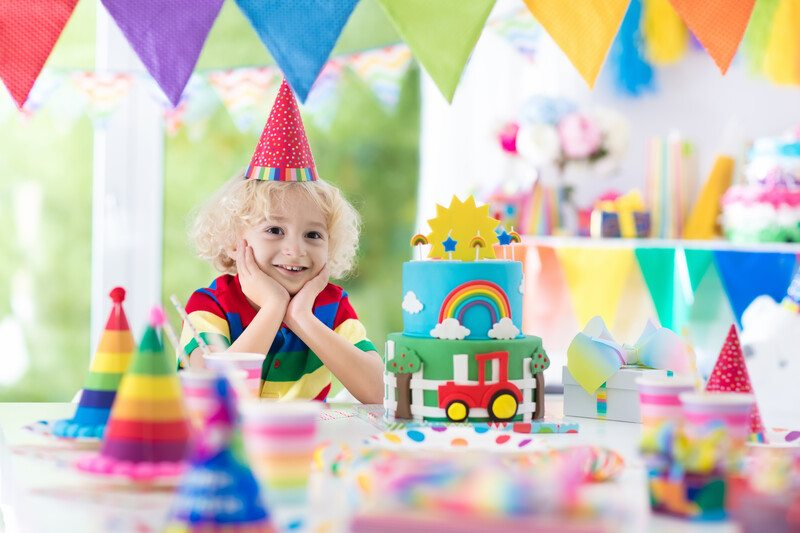This image shows a blonde child in a red party hat, sitting at the end of a table with his chin in his hands, surrounded by multicolored banners, toys, gift bags, and other party hats that designate each place setting, representing the best party affiliate programs.
