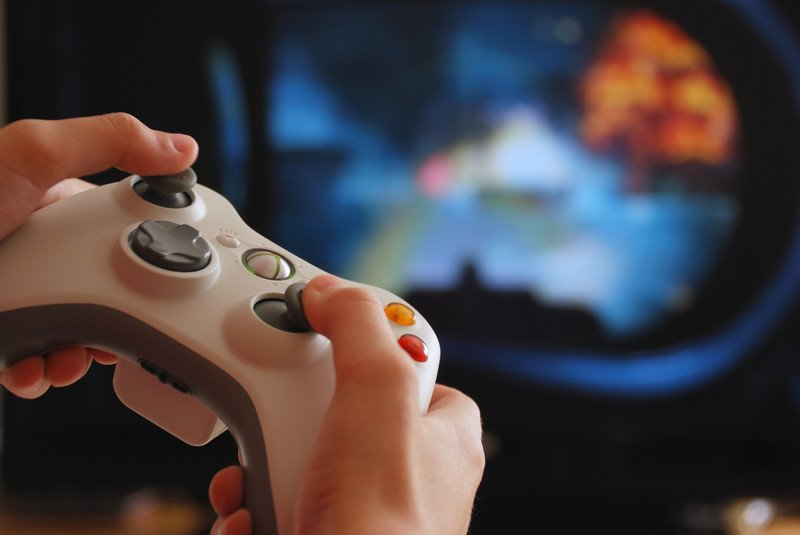 This picture shows a white video game controller, with gray buttons, in someone's hands in front of a screen with a blurry image of a video game in progress in colors of blue, green, white, and orange, representing the best streamer affiliate programs.