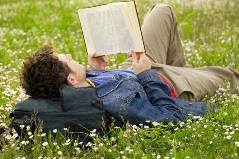 A young man lying in the grass reading a book