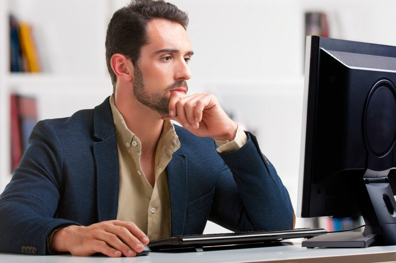 A man in a business suit sitting at his computer