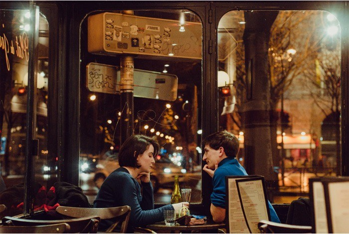 A young couple sitting in a coffee shop in the evening