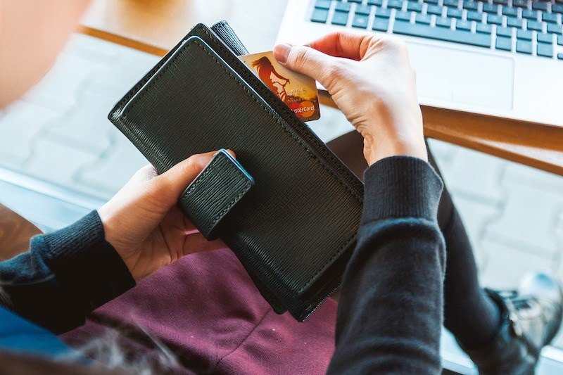 A woman pulling her credit card out of a wallet