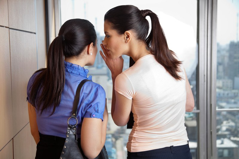 Two women gossiping with their backs to the camera