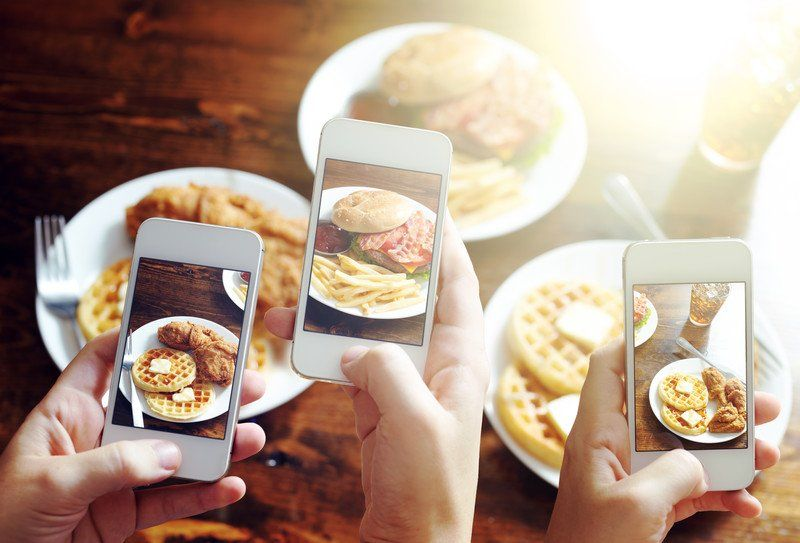 Three hands taking photos of food for Instagram
