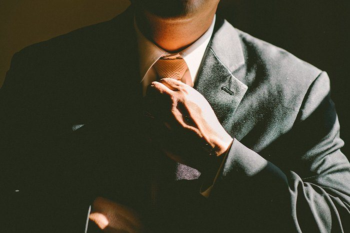 A close up image of a businessman doing up his tie