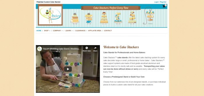 This screenshot of the home page for Cake Stackers has a pale yellow background with tiny white latticework and a main section with a white background, a blue and white striped banner that includes graphics of cakes in brown, blue, and green, a white navigation bar, a video image of a woman cutting a square tiered cake, and text in black and brown that describes what Cake Stackers is all about.