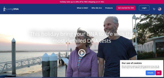 This screenshot of the home page for Living DNA has a red header announcing a holiday sale, a blue navigation bar with a red call to action button, and a large photo of an aging couple walking together along a lake's edge, smiling.