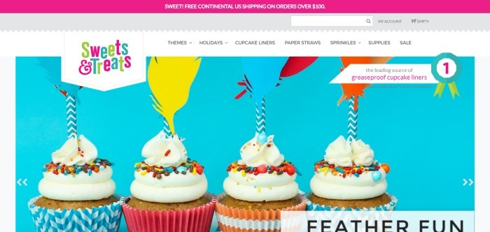 This screenshot of the home page for Sweets & Treats Boutique has a magenta bar at the top announcing free shipping, a white navigation bar, and a main section with a blue background featuring four cupcakes with white frosting and sprinkles in a variety of blue, pink, and orange cupcake liners, with paper feather and straw decorations in blue, yellow, red, and orange.