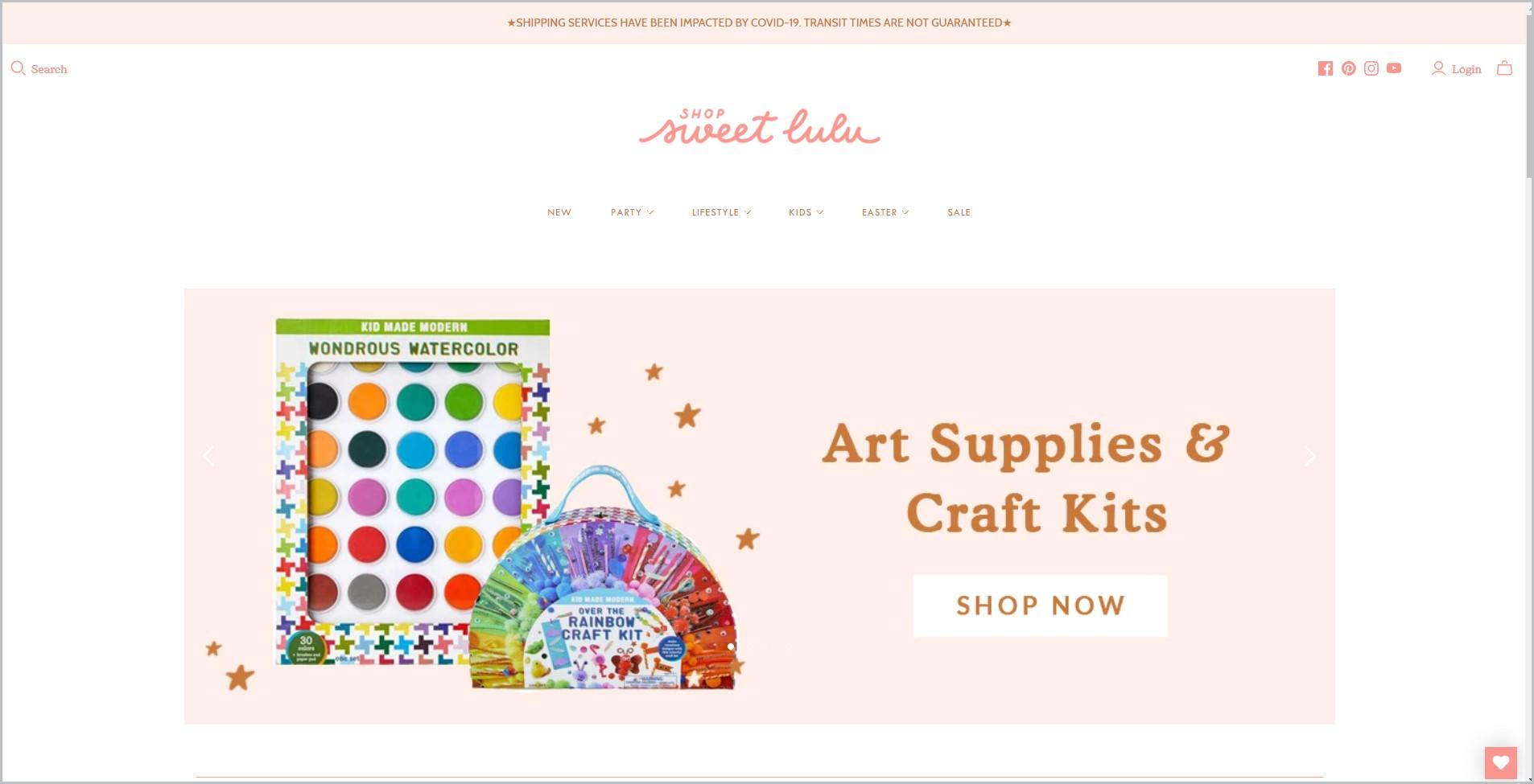 screenshot of Shop Sweet Lulu homepage with pale pink announcement bar, white header with the website's name and main navigation bar, it also showcases a picture of art supplies as main image