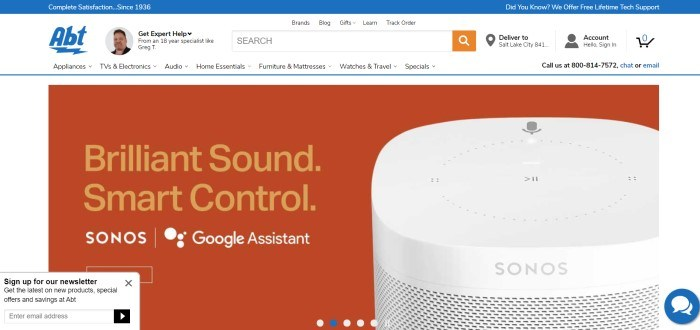 This screenshot of the home page for Abt Electronics has a white background and navigation bar, a blue header, and a large orange area with a photo of a Google assistant named Sonos, along with an advertisement for the Sonos.