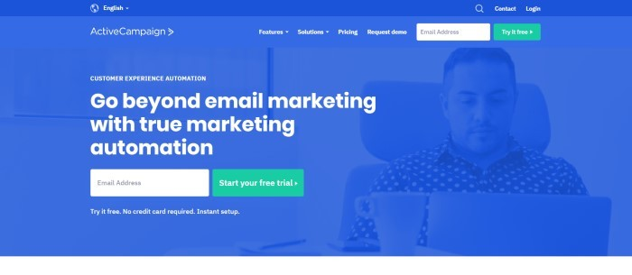 """This screenshot of the home page for Active Campaign has a royal blue background with a blue filtered photo of a man in a polka-dot shirt sitting in an office chair, looking at a laptop near a white coffee up, along with white wording that reads """"Go beyond email marketing with true marketing automation"""" and a two green call-to-action buttons."""