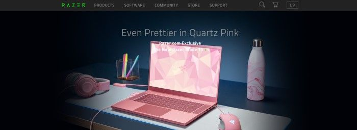 This screenshot of the home page for Razer has a black background with gray text and an image of a quartz-pink Razer Blade 15 laptop, along with a pink mouse, headset, water bottle, and a clear plastic pen holder with multi-colored pens, on a gray and black table.