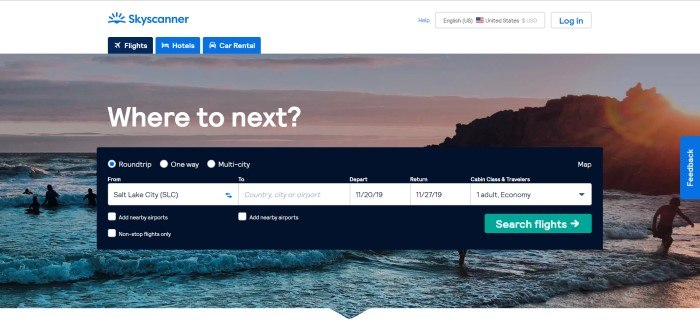 This screenshot of the home page for Skyscanner has a white header with a blue logo and blue navigation tabs above a photo of a seascape at sunset, along with a black search window and white wording that reads