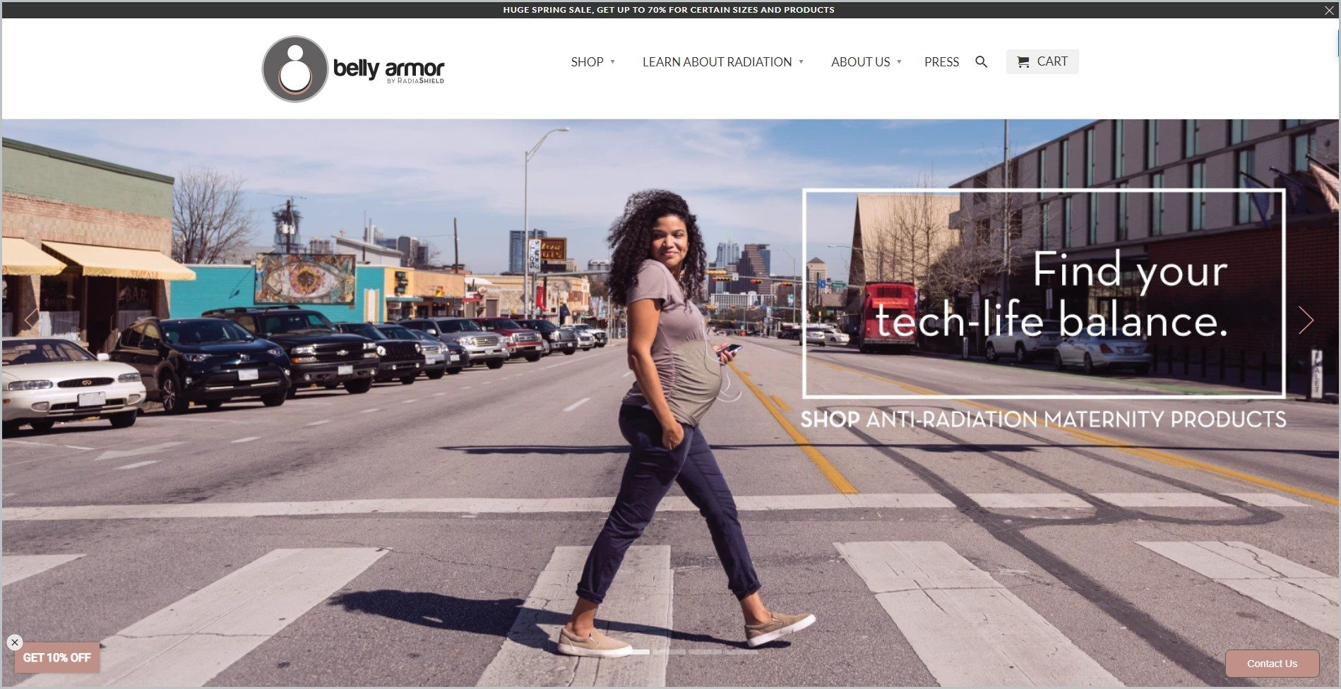 screenshot of Belly Armor homepage with black announcement bar, white header with the website's name and main navigation menu, it also showcases a smiling pregnant black woman, crossing a pedestrian lane