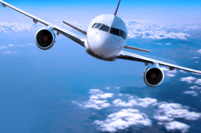 This image shows an oncoming white twin-engine aircraft in a blue sky above white clouds and water, representing the best airline affiliate programs.