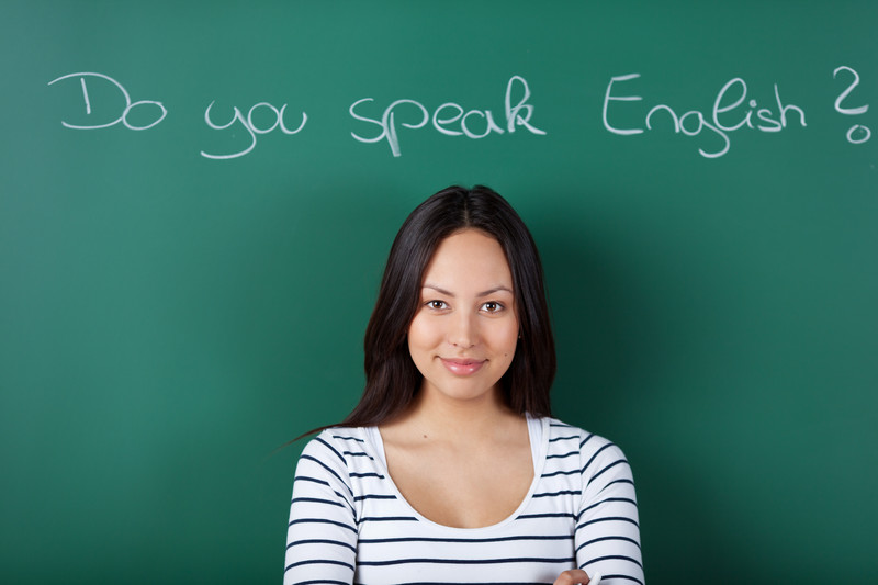 "This photo shows a smiling dark-haired woman in a white and black striped shirt standing in front of a green chalk board with the question ""Do you speak English?"" written on it in white chalk, representing the best ESL affiliate programs."