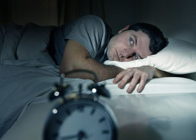 This image shows a man in a gray shirt, lying in bed with an unhappy expression on his face and wide eyes, as he looks toward the alarm clock on the nightstand next to him, representing the best sleep affiliate programs.