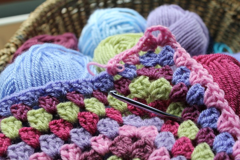 A crocheted blanket with various balls of wool and a crochet hook