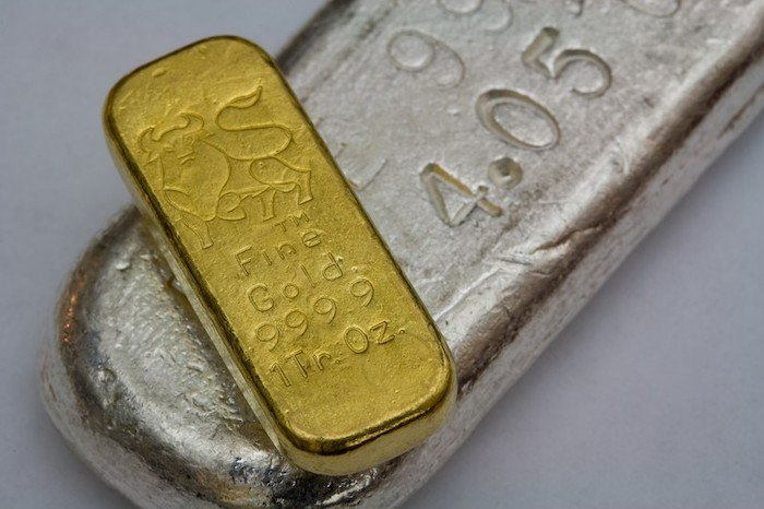 A stamped gold bar and silver bar on a table