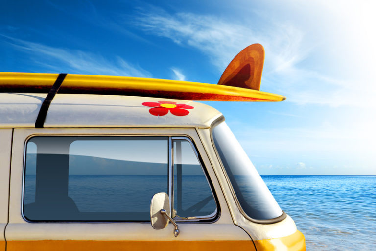 Image of a campervan with a surfboard on the roof