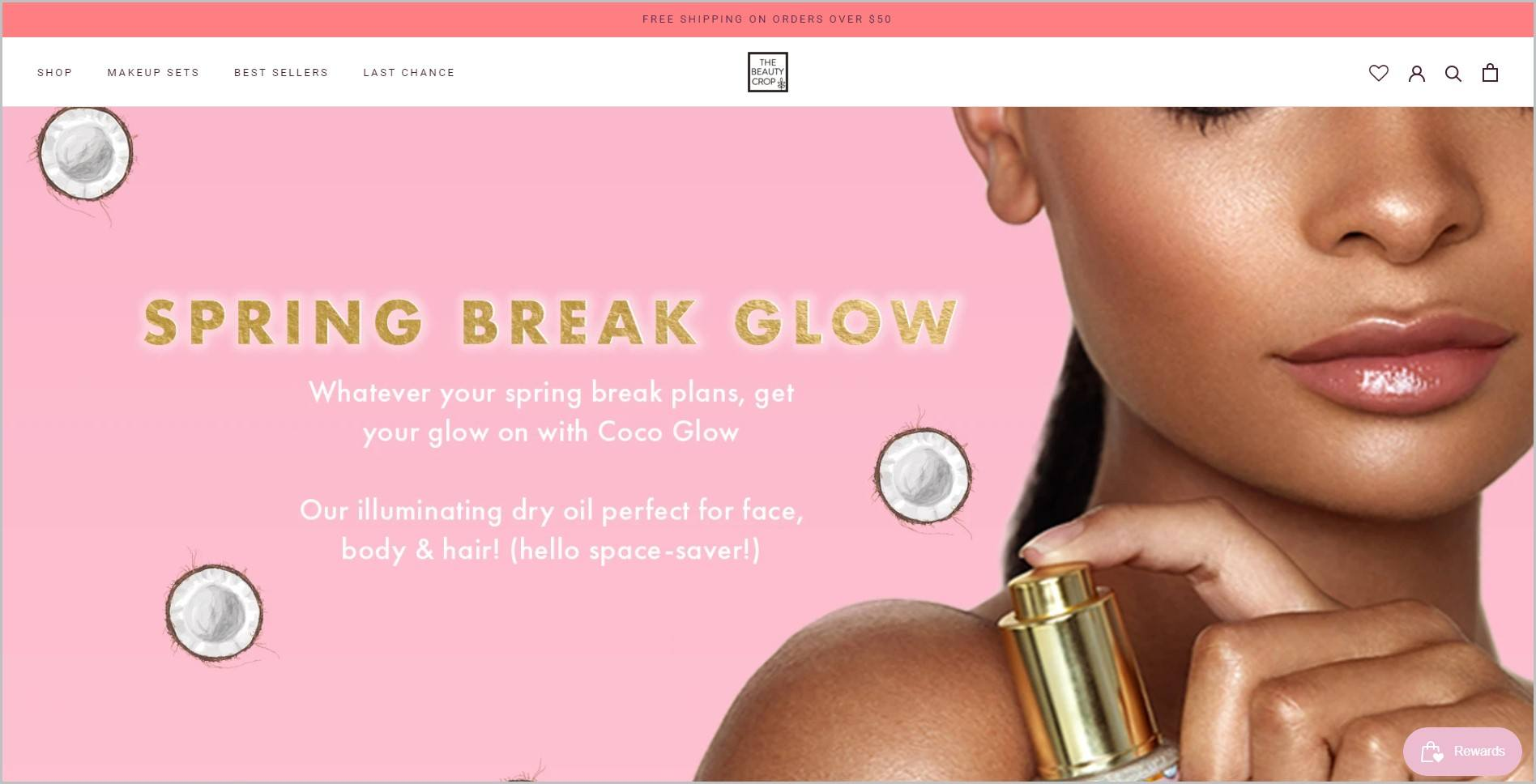screenshot of The Beauty Crop homepage, with coral announcement bar, white header with the website's name and main navigation menu, it showcases a black woman model holding a skincare product