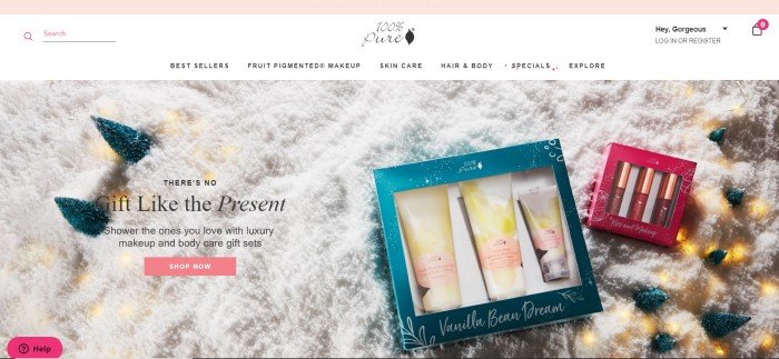 This screenshot of the home page for 100% Pure has a white navigation bar above an overhead photo of 100% pure gift sets lying on what appears to be snow and a pink call-to-action button.