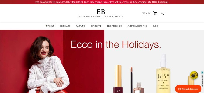 This screenshot of the home page for Ecco Bella has a red header announcing a sale, a white navigation bar, a photo of a smiling brown-haired woman with perfect makeup and a white sweater in front of a red background on the left side of the page, and a photo of Ecco Bella products against a white background on the right side of the page.