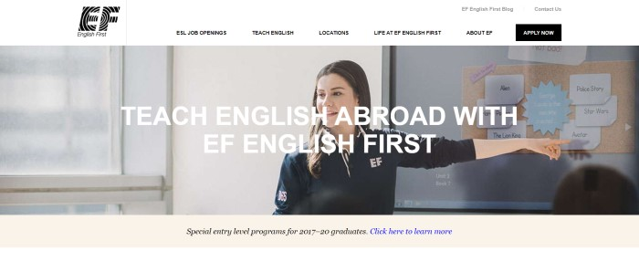 "This screenshot of the home page for English First has a white header and navigation bar above a photo of a smiling woman in a dark English First uniform jacket, pointing at some words on a blackboard while she looks out over a classroom, along with white text that reads ""Teach English abroad with EF English First."""