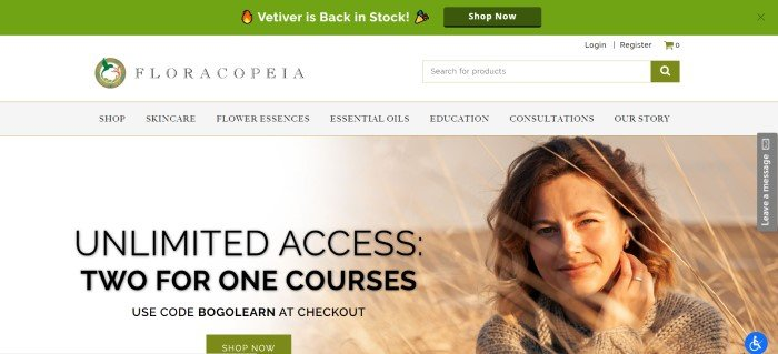 This screenshot of the home page for Floracopeia has a green header announcing a flower essence is back in stock, a white area with a search bar and the Floracopeia logo, a gray navigation bar, and a filtered photo of a smiling brunette woman in a field of tall grass, along with black text offering a two-for-one coupon code for educational courses.