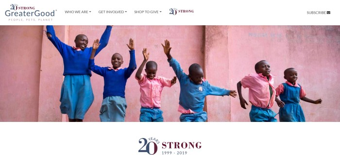 This screenshot of the home page for Greater Good has a photo of a row of young dark skinned boys on royal blue, light blue, and pink shirts dancing with arms raised against a backdrop of a pink cement wall, along with a white navigation bar.