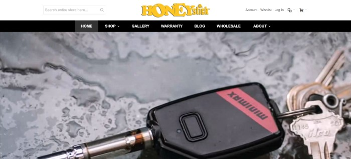 This screenshot of the home page for HoneyStick has a white header with a yellow logo, a black navigation bar, and a black and red minimax vaporizer keychain with keys lying on what looks like a gray table with water spilled on it.