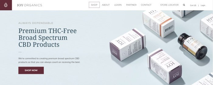 This screenshot of the home page for Joy Organics has a white navigation bar above a light gray section showing small boxes containing Joy Organics products, along with text in black and gray announcing premium THC-free CBD products and a burgundy call-to-action button.