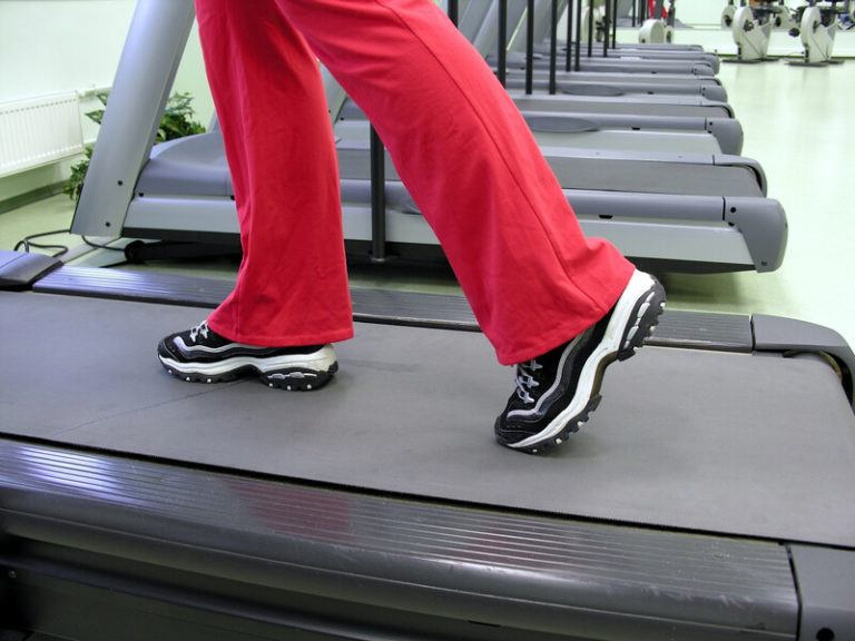 This image shows a row of gray treadmills, as well as the legs and feet of someone in red pants and black and white sneakers walking on the nearest treadmill, representing the best exercise machine affiliate programs.