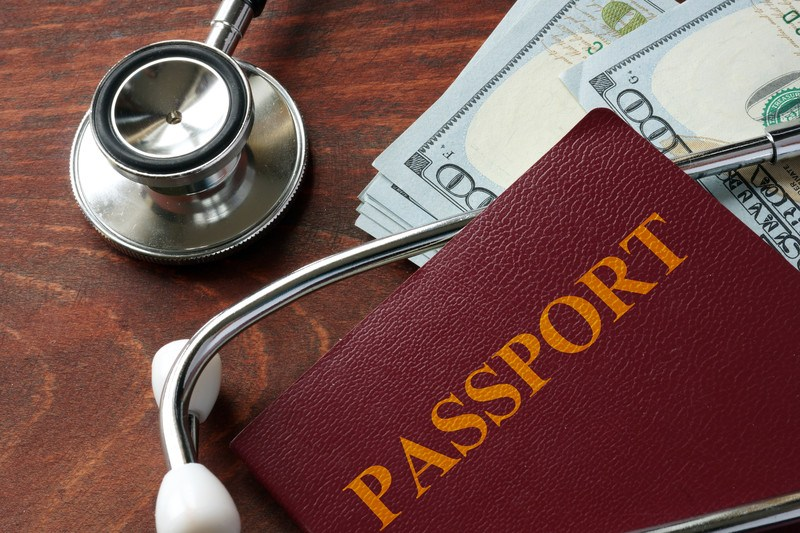 This image shows the top of a wooden desk with a stethoscope, a brown passport cover, and a stack of $100 bills, representing the best medical vacation affiliate programs.