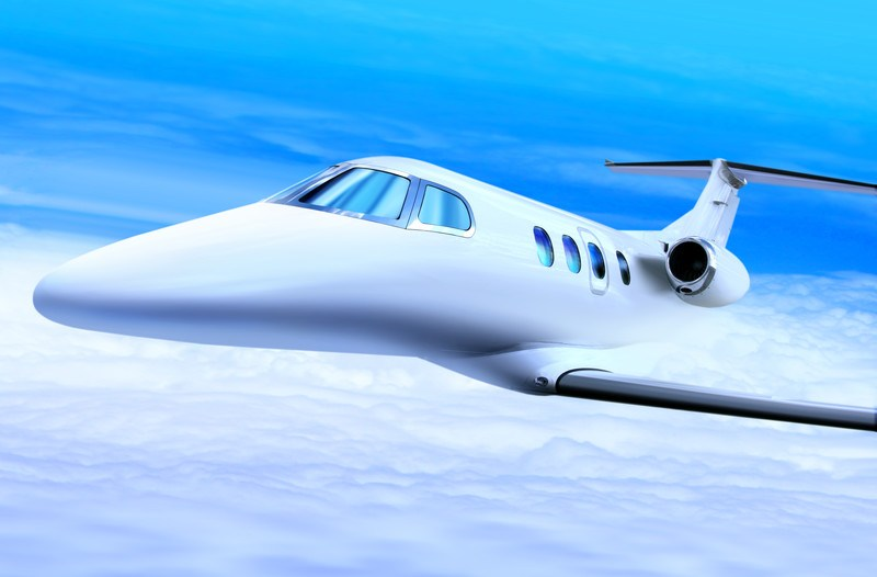 This image shows a white jet flying in a blue sky above the clouds, representing the best private jet charter affiliate programs.