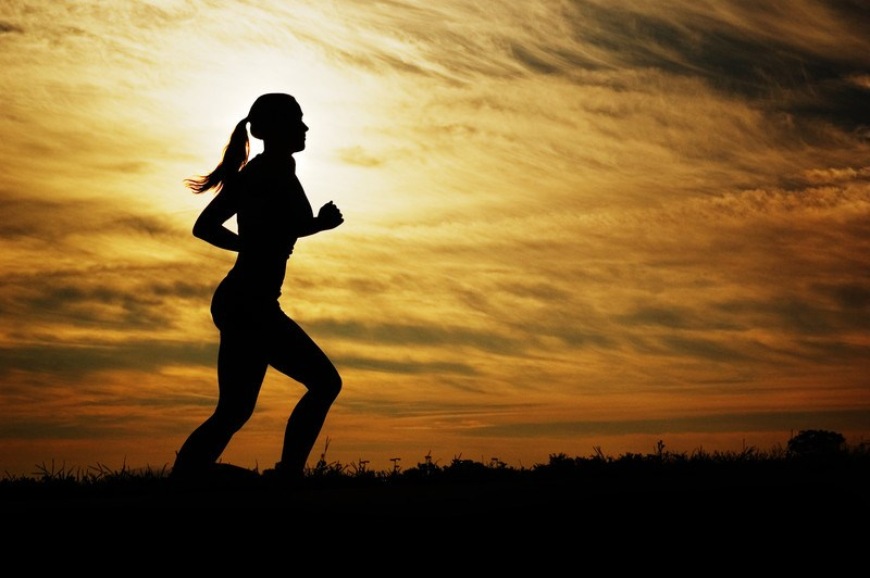 This photo shows the silhouette of a woman in a ponytail running against a yellow and orange sunset, representing the best women's fitness affiliate programs.