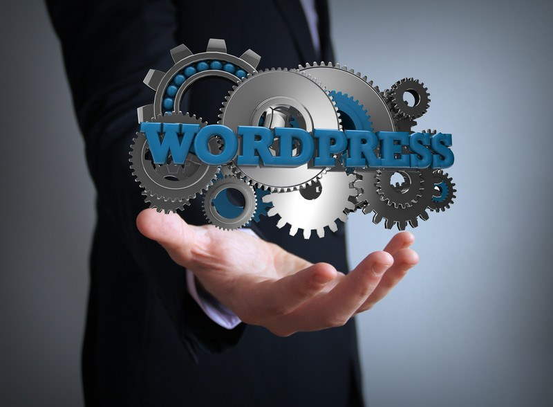 This image shows the side view of a businessman in a dark suit with an outstretched hand below a hovering set of gears and the word 'WordPress,' representing the best WordPress Theme affiliate programs.