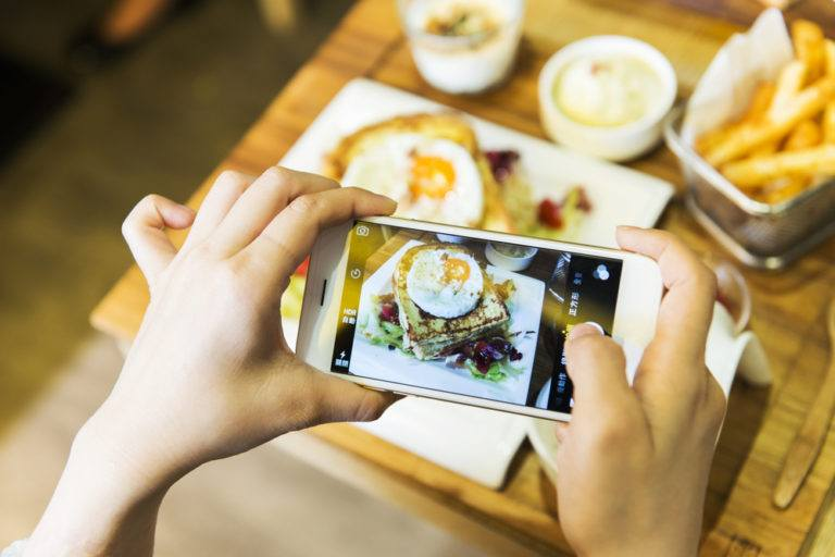 A person using their phone to take a photo of their meal
