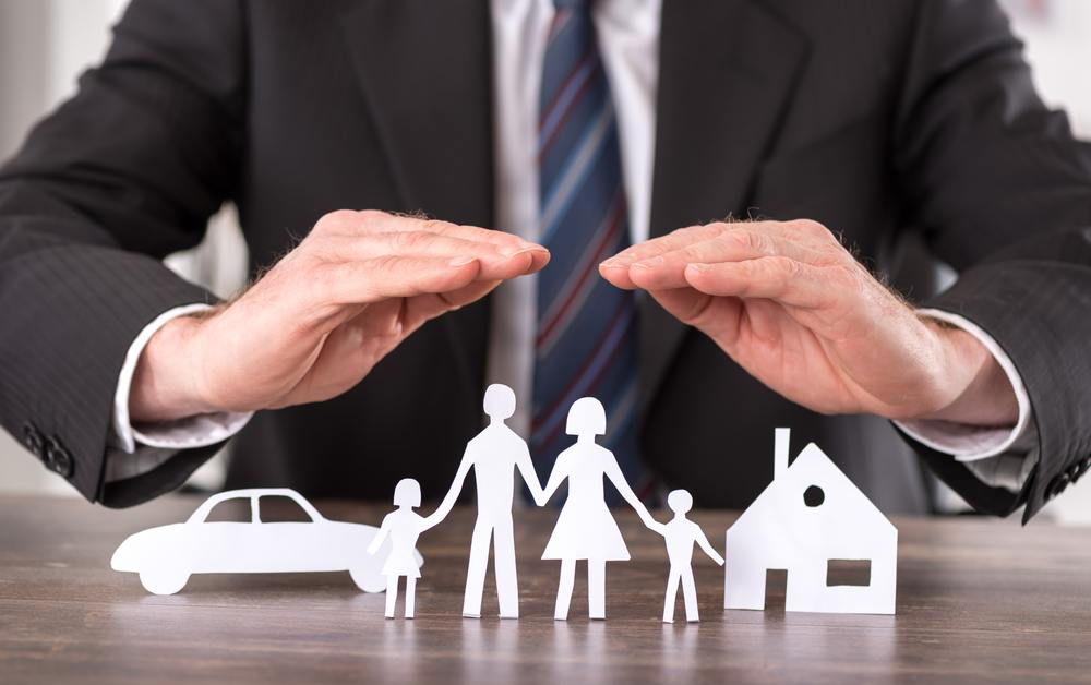 The torso of a businessman with siluoettes of a family, car and house