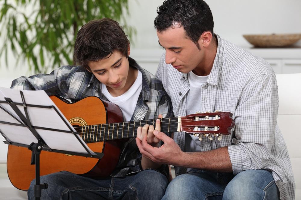 A man teaching a boy how to play guitar