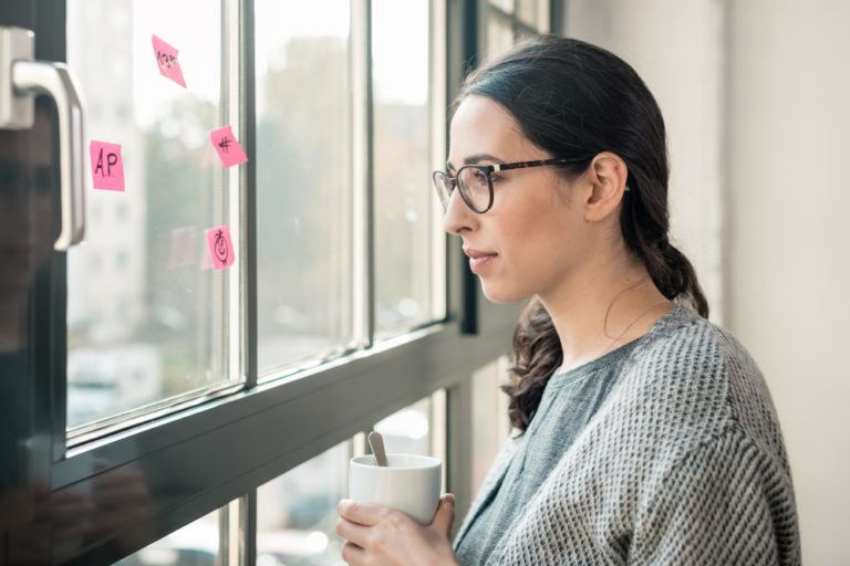 A black haired woman in glasses looking out the window