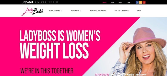 This screenshot of the home page for LadyBoss has a black and white header with a navigation bar and a pink and black logo, above a hot pink triangle with white text announcing women's weight loss and a photo of a smiling blonde woman in a pink hat.