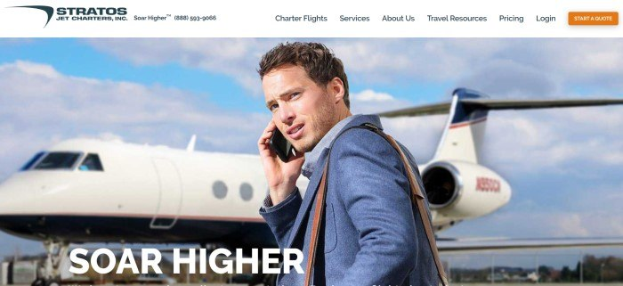 """This screenshot of the home page for Stratos Jet Charters shows a young man with brown hair and a blue suit talking on a cell phone as he is about to get on a white jet, behind white text that reads """"Soar higher."""""""