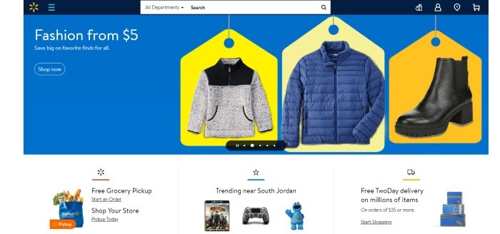 This screenshot of the home page for Walmart has a dark blue header with a search bar and a royal blue main section with bright yellow price tags behind various jackets in black, white, and blue, along with white text announcing fashions on sale.