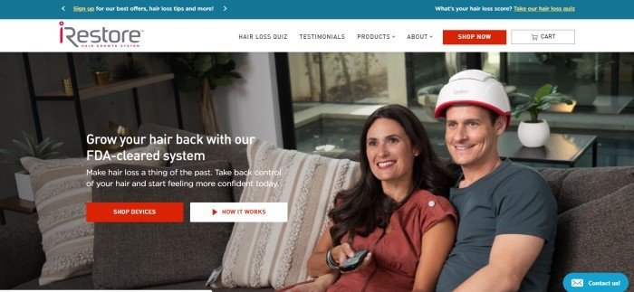 This screenshot of the home page for iRestore Laser shows a smiling woman with brown hair and a russet shirt holding a television remote control in her hand, while she snuggles next to a smiling man in a charcoal-colored tee shirt and an iRestore helmet on a brown and white couch.