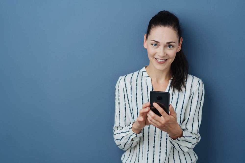 A woman using her phone against a blue background