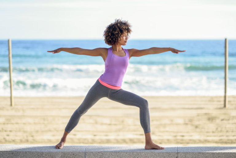 This image shows a black woman with an Afro hairstyle in a purple and pink workout top and gray leggings holding warrior pose on a beach, representing the best activewear affiliate programs.